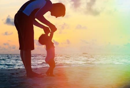 Silhouet van vader en weinig dochter lopen op zonsondergang strand