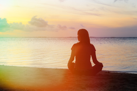 sit: young woman meditation on sunset tropical beach