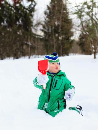 digging: little boy digging winter snow, winter fun Stock Photo