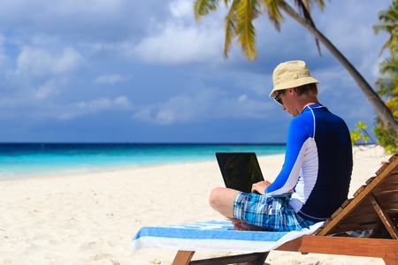 working lifestyle: man with laptop on tropical beach vacation