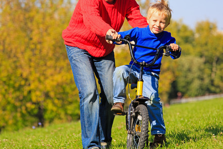 father teaches son to ride bicycle outdoors