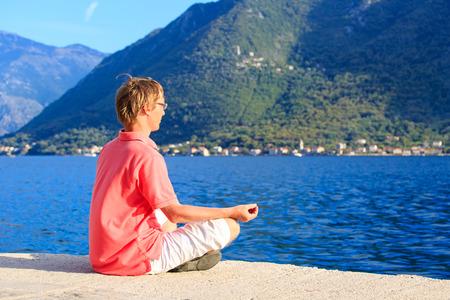 man meditating: young man meditating at summer sea coast