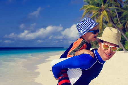 family day: father and little son on shoulders on tropical beach