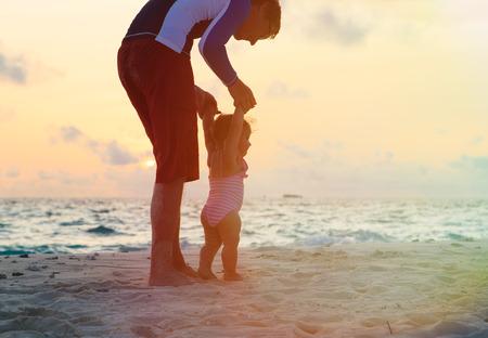 padre e hija: Silueta del padre y la pequeña hija caminando en la playa de la puesta del sol