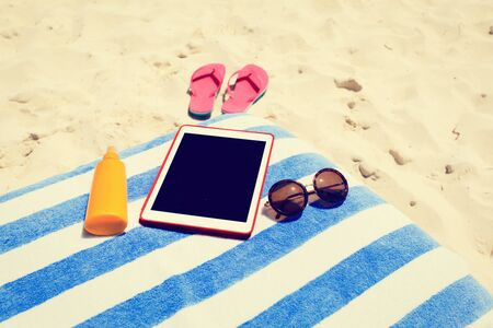 suncream: Suncream, slippers and touch pad on the beach, summer vacation Stock Photo