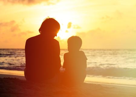 해변에서 석양을보고 아버지와 작은 아들의 실루엣