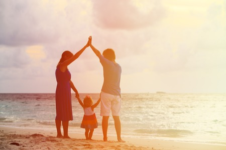 holding mother's hand: Happy family together at sunset. Mother, father and little child