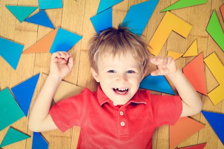 boy: happy little boy with puzzle toys on wooden floor, early learning Stock Photo