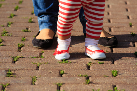 teaching adult: mother helping daughter to make first steps in summer park Stock Photo