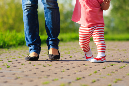 teaching adult: mother teaching little daughter to walk in summer park Stock Photo