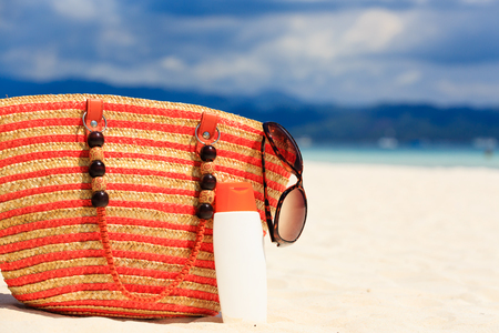 suncream: bag, sun glasses and suncream on tropical beach