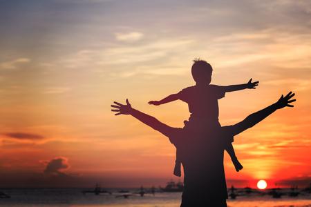 일몰 해변에서 노는 아버지와 아들