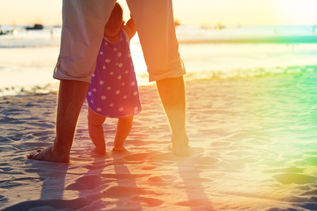 teaching and learning: father and little daughter learning to walk on sunset beach
