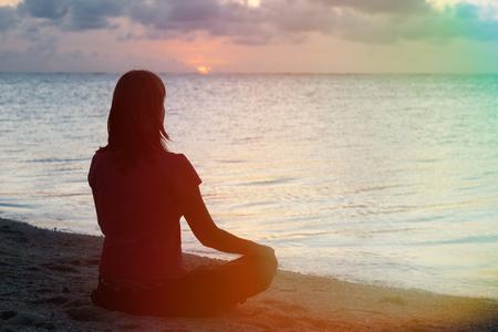 サンセットの熱帯ビーチで若い女性瞑想