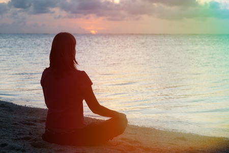 young woman meditation on sunset tropical beach