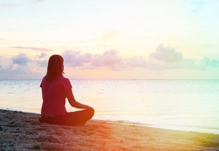 personas pensando: mujer joven meditación en la puesta del sol playa tropical