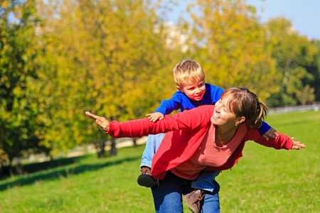ouside: mother and son flying in autumn park, family fun
