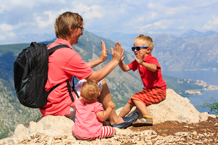 alp: father with kids having fun on vacation in mountains