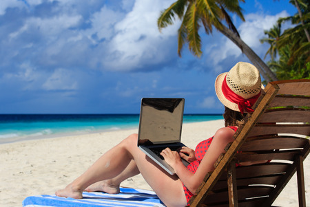 woman with laptop on tropical beach vacation Reklamní fotografie