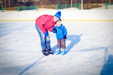 boy skating: little boy skating with parent, first skating lesson