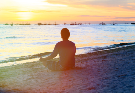 people human mind: Silhouette of young man meditating at sunset beach Stock Photo