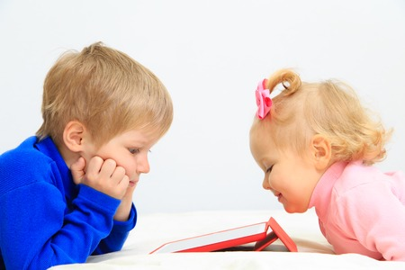 early education: little boy and toddler girl using touch pad, early education and learning