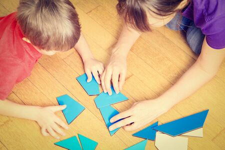 child hand: hands of teacher and child playing with geometric shapes, early learning