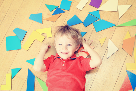 early learning: happy little boy with puzzle toys on wooden floor, early learning Foto de archivo
