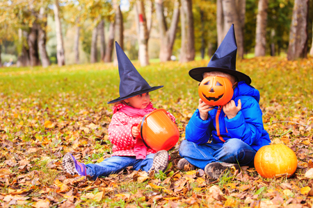 treating: kids in halloween costume play at autumn park, kids trick or treating