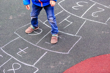 lifestyle outdoors: kid playing hopscotch on playground outdoors, children outdoor activities