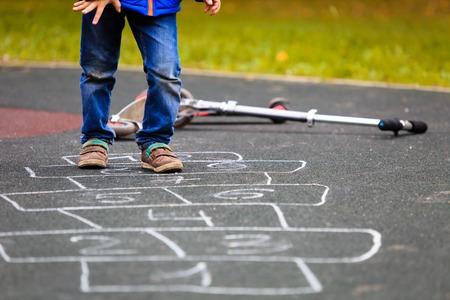 ni�os jugando: ni�o jugando a la rayuela en el patio al aire libre, los ni�os actividades al aire libre Foto de archivo