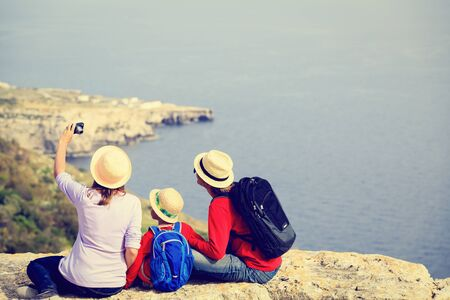 family with small kid making selfie while travel in scenic summer mountains Archivio Fotografico