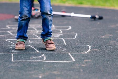 al aire libre: niño jugando a la rayuela en el patio al aire libre, los niños actividades al aire libre Foto de archivo