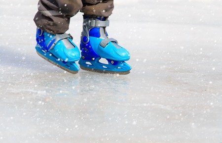 ice cold: child feet learning to skate on ice in winter snow Stock Photo