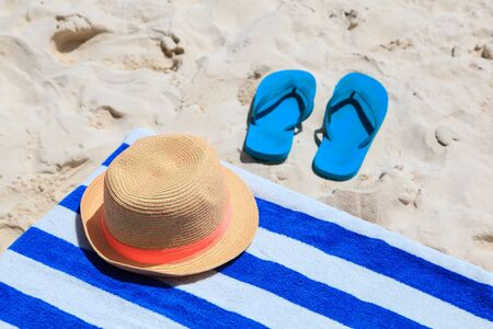 flip flops: Straw hat, towel and flip flops on a tropical sand beach