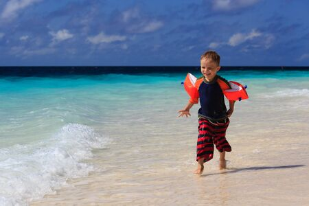 armbands: little boy running on sand tropical beach