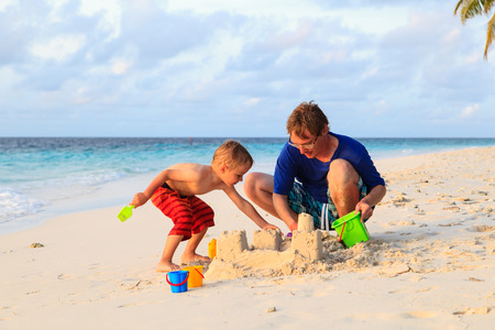 sandcastle: father and son building sandcastle on tropical beach