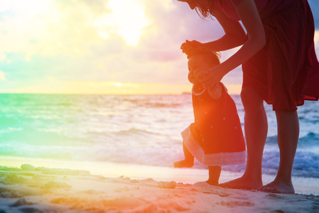 mother and children: madre y peque�a hija caminando en la playa de arena al atardecer