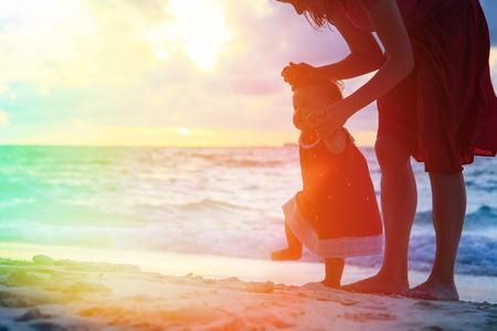 moeder en dochter lopen op zand strand bij zonsondergang Stockfoto