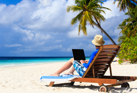 man with laptop on tropical beach vacation