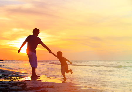 man flying: silhouettes of father and son having fun on sunset beach Stock Photo