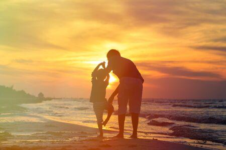 silueta hombre: siluetas de padre e hijo haciendo yoga en el mar la puesta del sol Foto de archivo