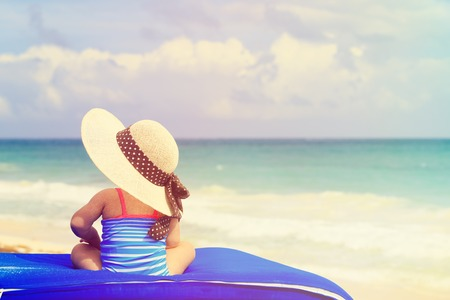 summer beach: little girl in big hat on summer tropical beach