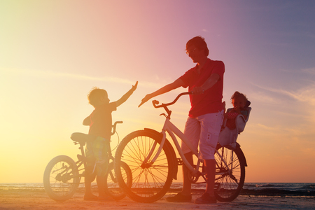 happy family: silhouette of father with two kids on bikes at sunset