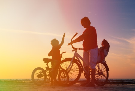 outdoor activities: silhouette of father with two kids on bikes at sunset