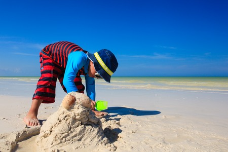 children sandcastle: little boy digging sand on tropical sand beach