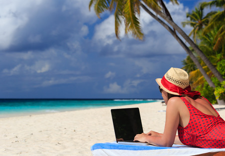 vacaton: woman with laptop on tropical beach vacaton Stock Photo