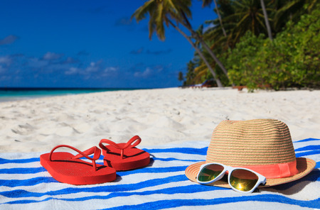 caribbean beach: hat, sun glasses and flip flops on a tropical beach, vacation concept