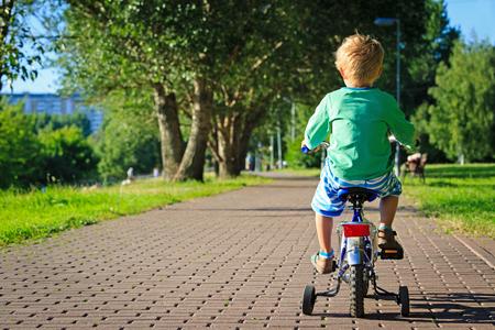 children learning: little boy riding bike in summer park Stock Photo