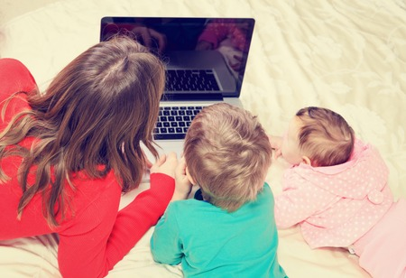 early education: teacher and kids looking at laptop, early education and technology